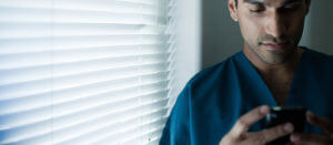 man in blue scrubs looking down at phone